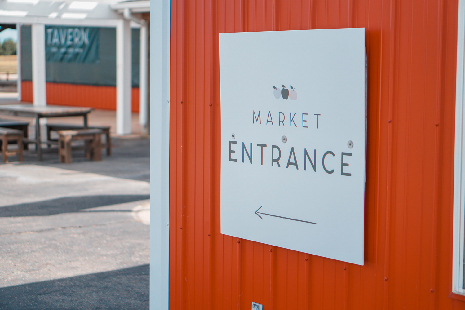 """white sign on the side of barn saying """"market entrance"""" with an arrow and cute apple illustration"""