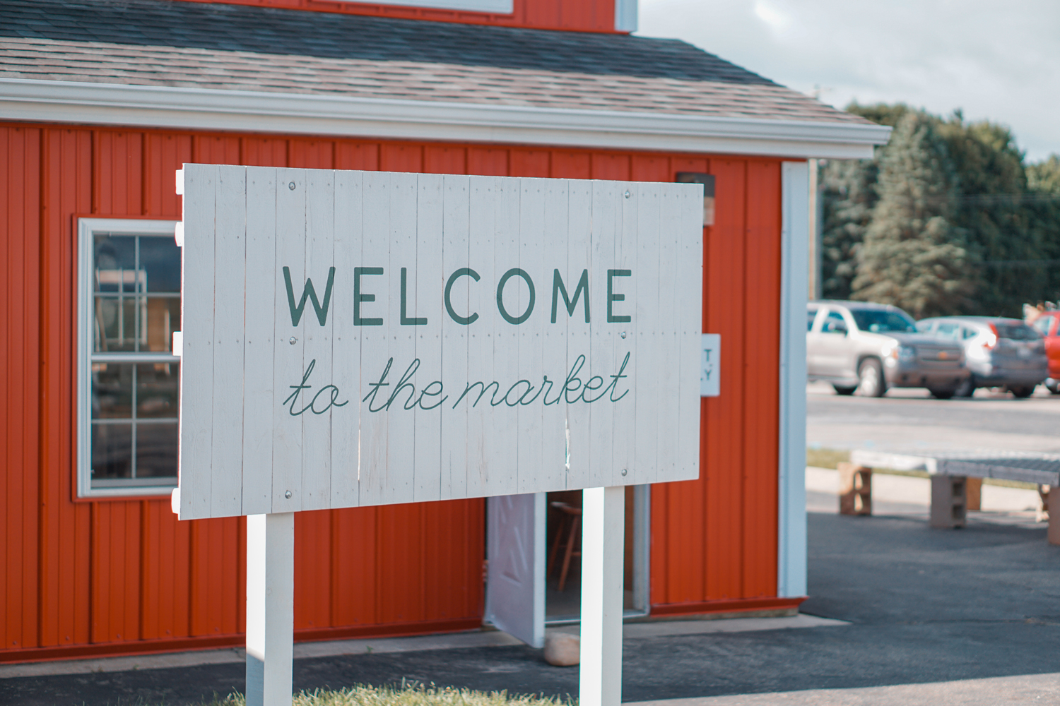 "white wooden sign saying ""welcome to the market"" in front of farm in Greenville michigan"