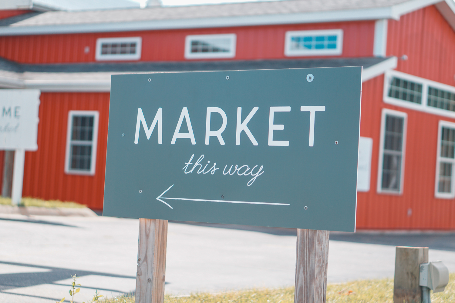 "green sign saying ""market this way"" with an arrow in front of a farm"