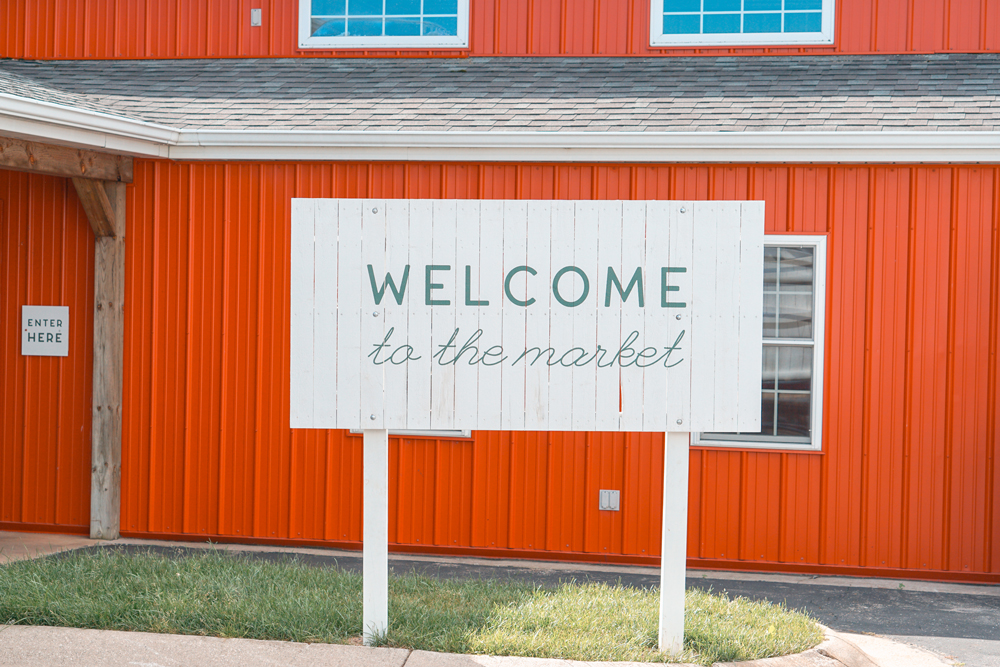 "beautiful white wood sign that says ""welcome to the market"" in hand-drawn font design in front of farm in Greenville michigan"