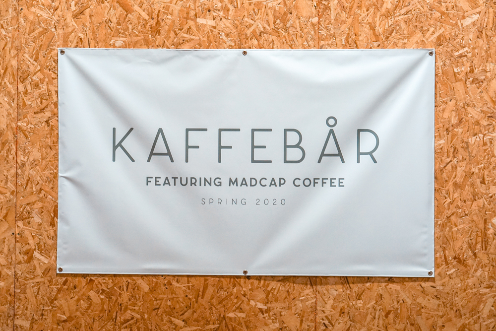 "coffee shop sign saying ""kaffebar featuring madcap coffee, spring 2020"""
