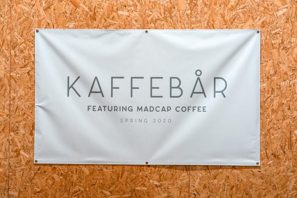 "coffee shop sign saying ""kaffebar featuring madcap coffee, spring 2020"""