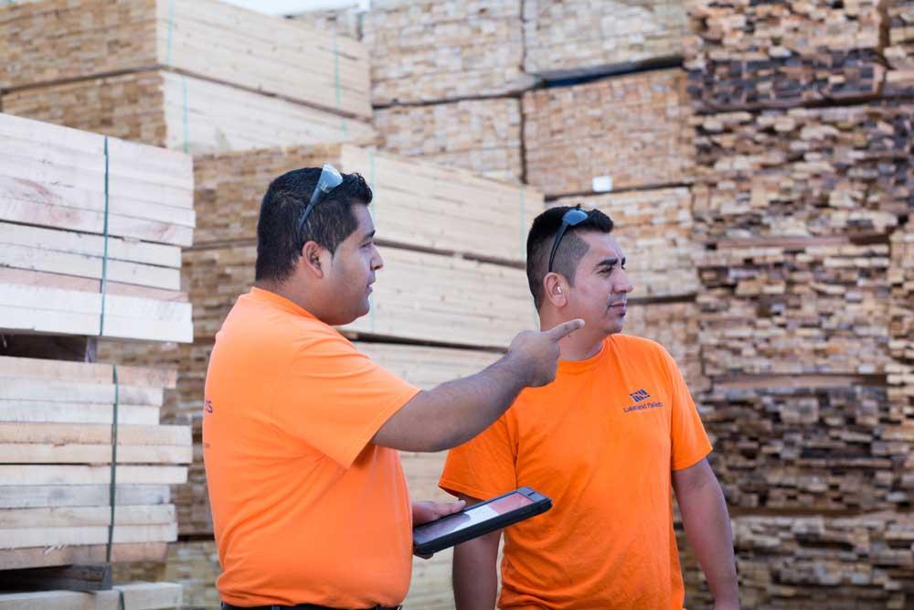 portrait of two men in pallet yard holding iPad wearing orange shirts