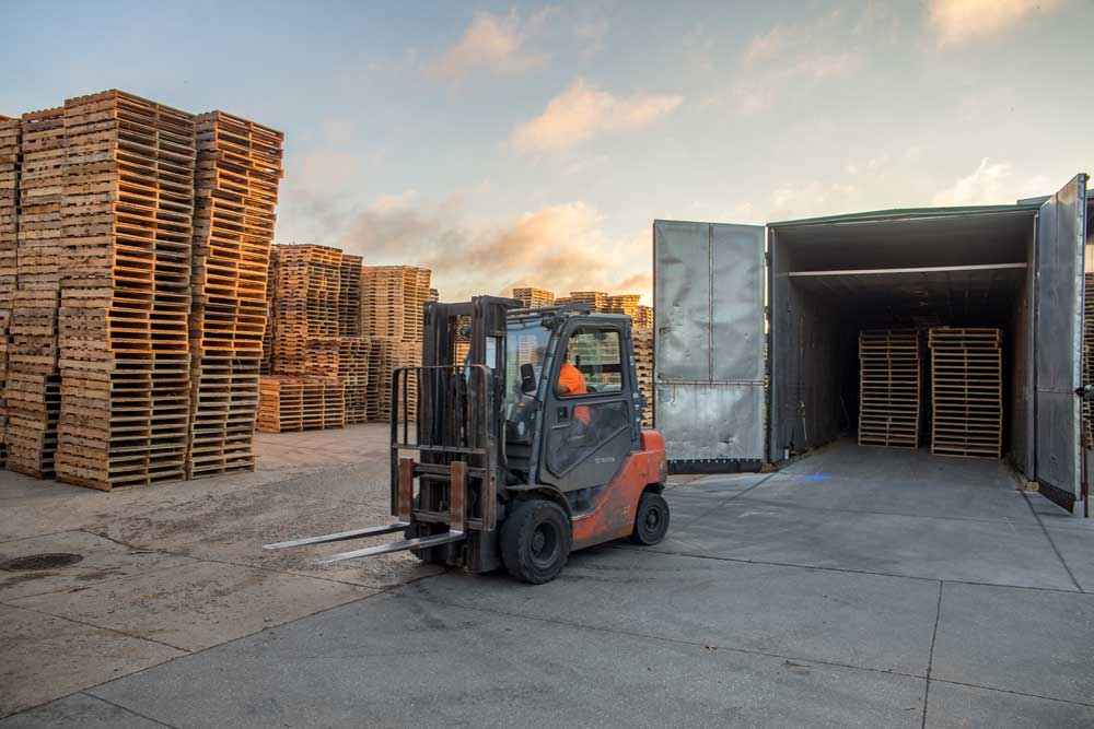 image of forklift in pallet yard in front of kiln