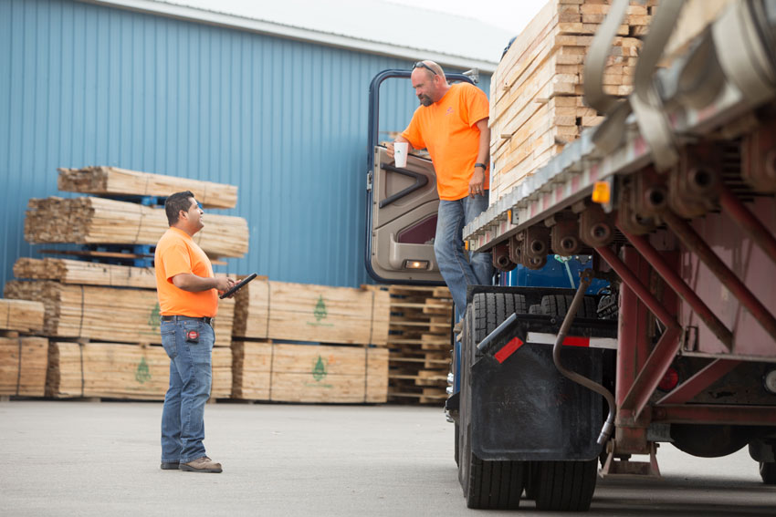 image of two employees standing in pallet yard discussing shipment next to truck loaded with pallets.