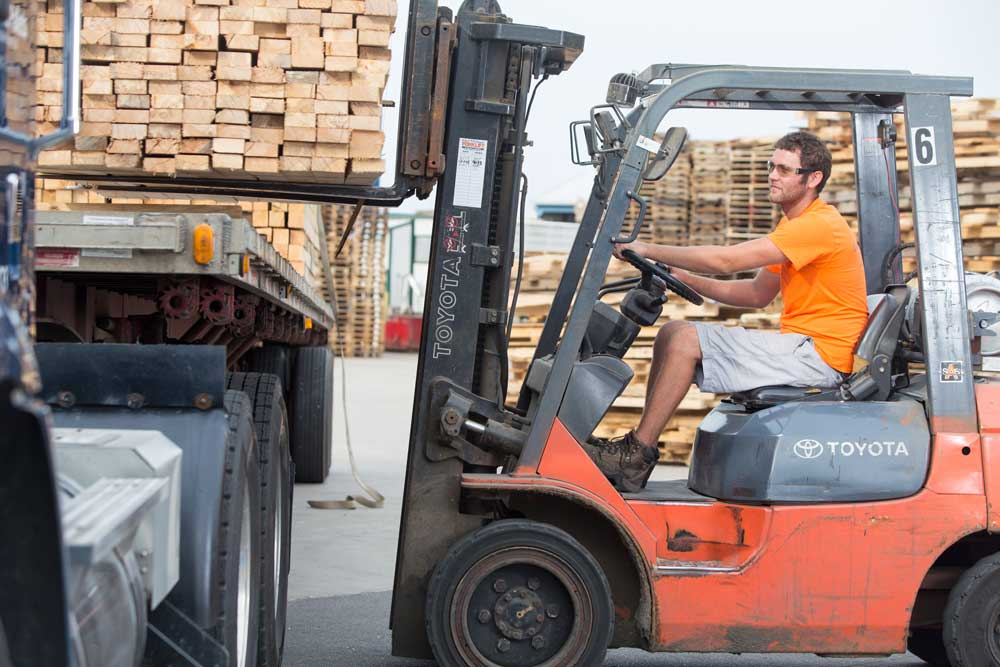 custom photography of employee drives a forklift and loads pallets onto a truck for transport at pallet company in Grand Rapids, Michigan