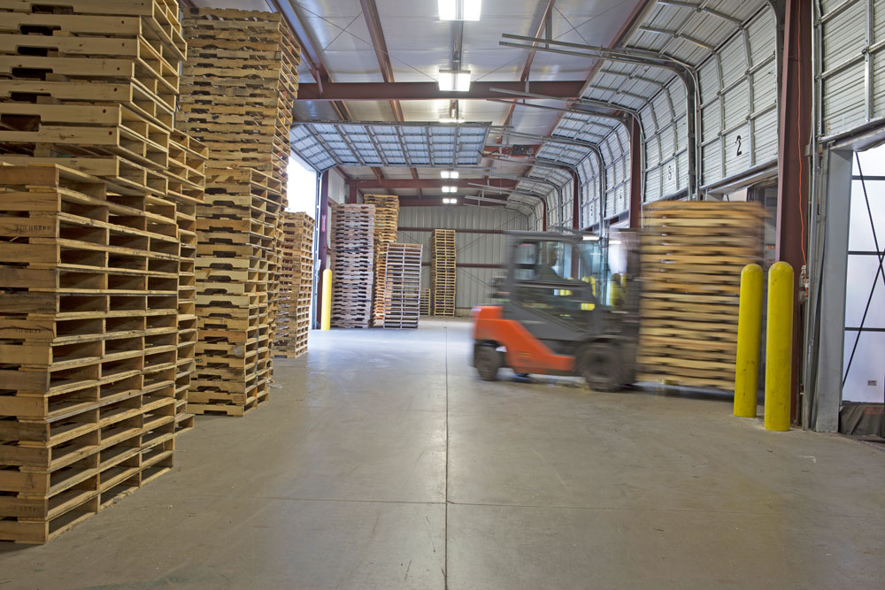 photo of pallet storage area with forklift moving in a blur at lakeland pallets in Grand Rapids, Michigan