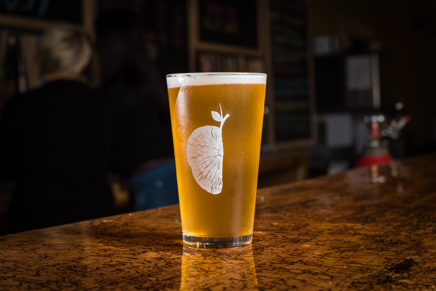rustic woodcut apple logo for a brewery on a pint glass of beer